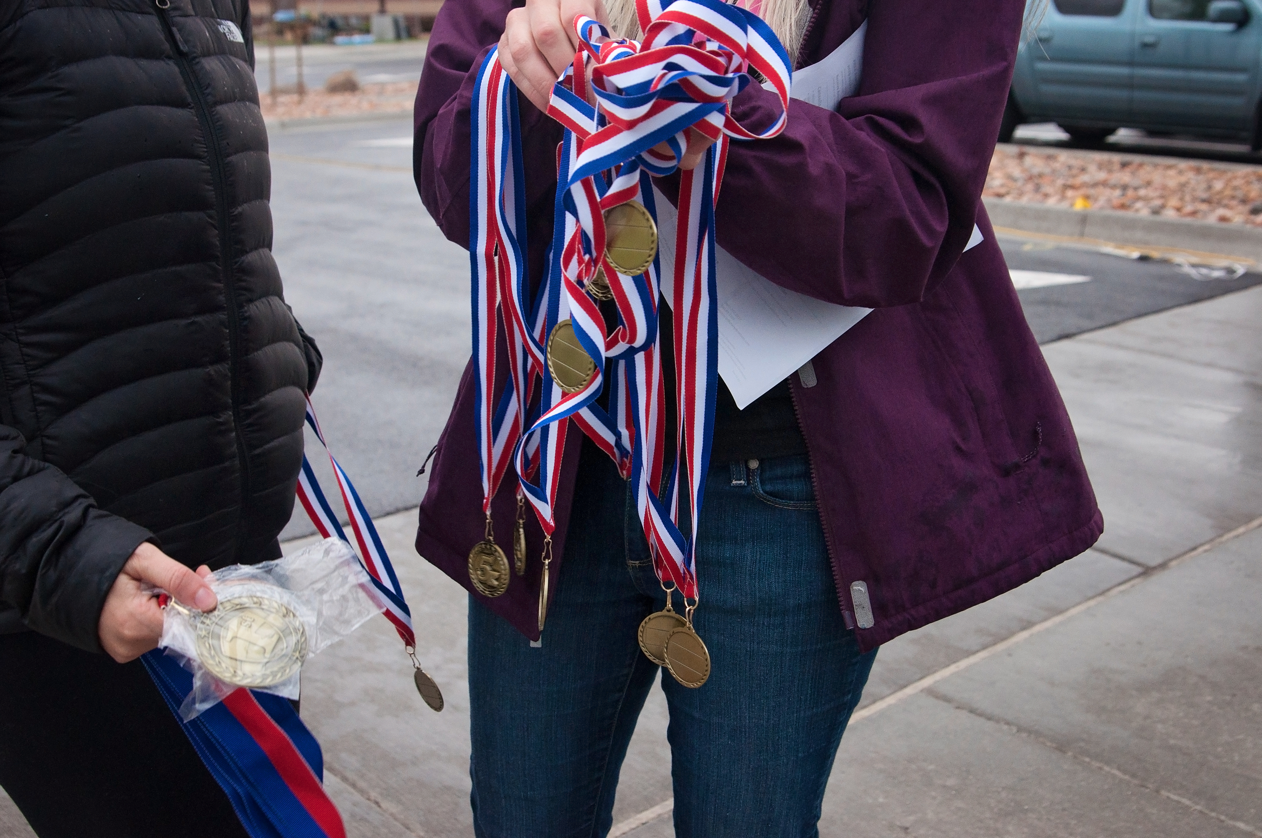 Rescue Run-37 | How Much is a 5K by popular Utah lifestyle blogger, Kara Metta: image of a woman holding a bunch of medals at the Rescue Run marathon.