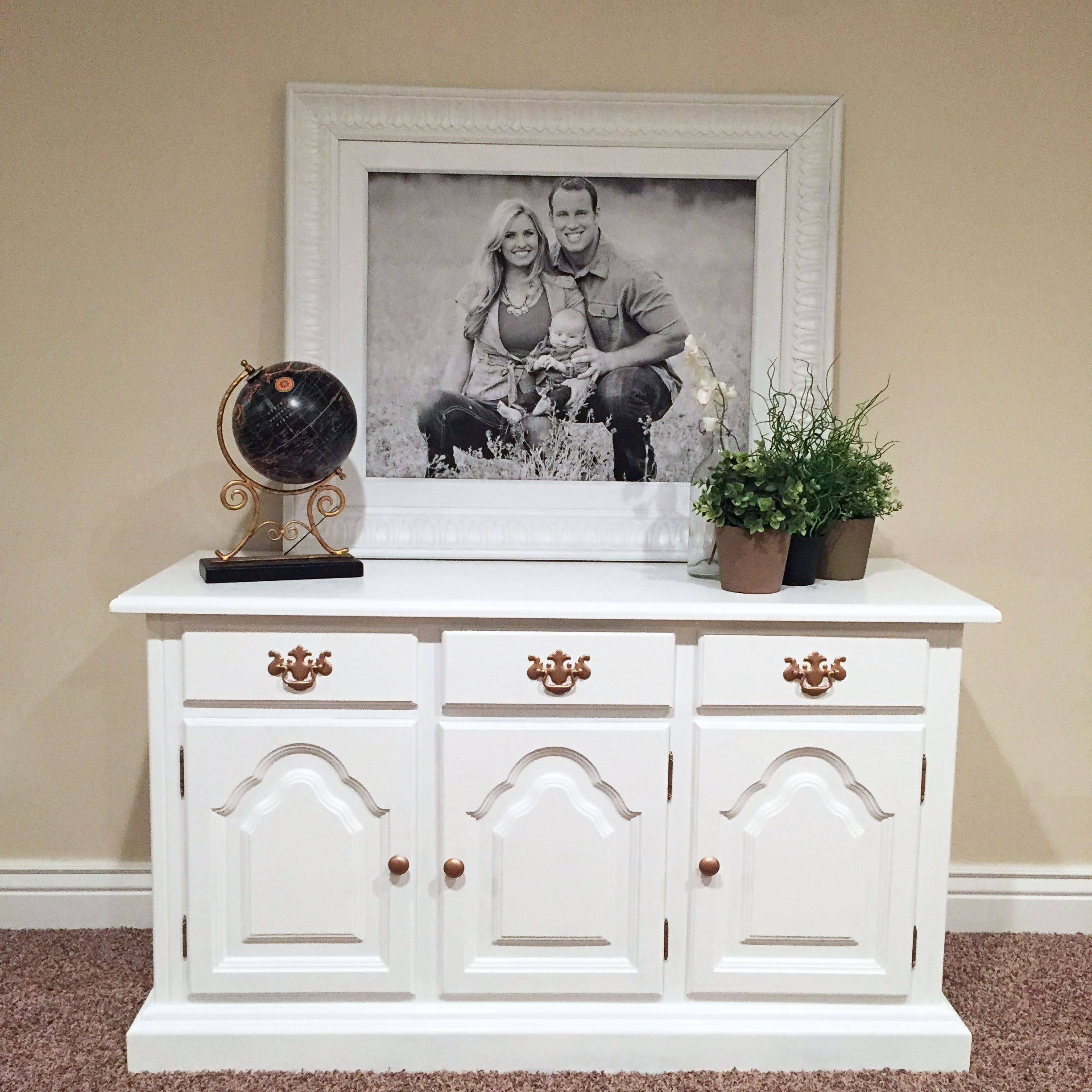 Buffet / dresser upcycle. Love the spray painted rose gold hardware! | Upcycled Buffet by popular Utah lifestyle blogger, Kara Metta: image of a white buffet with a black globe, faux plants, and a large black and white family photo on it.
