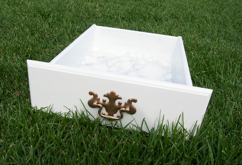 Marble drawer liner contact paper. Chic way to update furniture. | Upcycled Buffet by popular Utah lifestyle blogger, Kara Metta: image of a white buffet drawer with a gold pull handle.