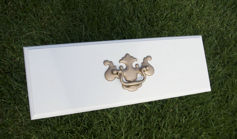 Rose gold spray paint to update old hardware.   Upcycled Buffet by popular Utah lifestyle blogger, Kara Metta: image of a white buffet drawer with a gold pull handle.