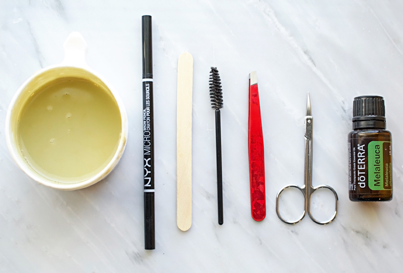 Supplies for waxing your eyebrows at home. | How to Wax Your Eyebrows at Home by Popular Utah beauty blogger, Kara Metta: image of Surgi-Wax, NYX Micro eyebrow pencil, wooden applicator stick, mascara wand, tweezers, cuticle clippers, and DoTerra Melaleuca oil.