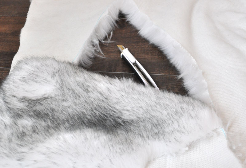 Tip: when working with faux fur, always cut from the back using an Xacto knife. This will be much easier and prevent you from cutting the fur short in random places.#sewingtip | Faux Fur Stole Pattern by popular Utah sewing blog, Kara Metta: image of Joann Fashion Faux Fox Fur Fabric Silver and a X-acto knife.