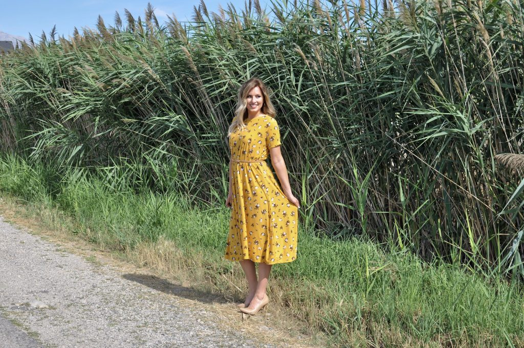 Easy t-shirt dress tutorial. Only 3 pattern pieces--front, back, and neckband. Only takes one afternoon .DIY Dress Tutorial // Sew a Dress without a Pattern | DIY Dress by popular Utah sewing blogger, Kara Metta: image of a woman standing outside and wearing a  yellow floral DIY t-shirt dress.