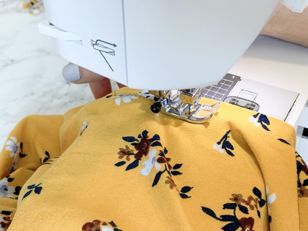 Easy t-shirt dress tutorial. Only 3 pattern pieces--front, back, and neckband. Only takes one afternoon. | DIY Dress by popular Utah sewing blogger, Kara Metta: image of a woman sewing a DIY t-shirt dress.