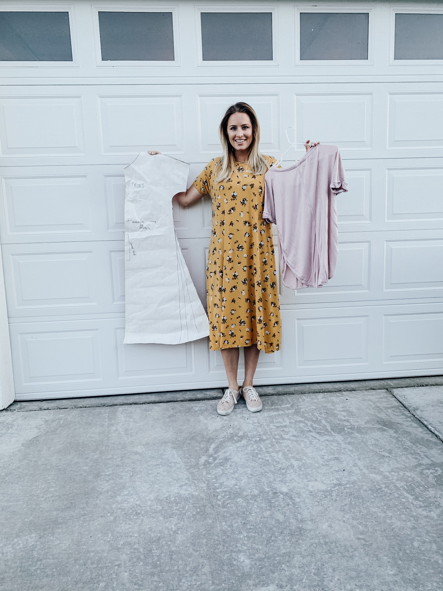 Woman wearing dress, holding dress pattern. | DIY Dress by popular Utah sewing blogger, Kara Metta: image of a woman standing outside and wearing a  yellow floral DIY t-shirt dress.
