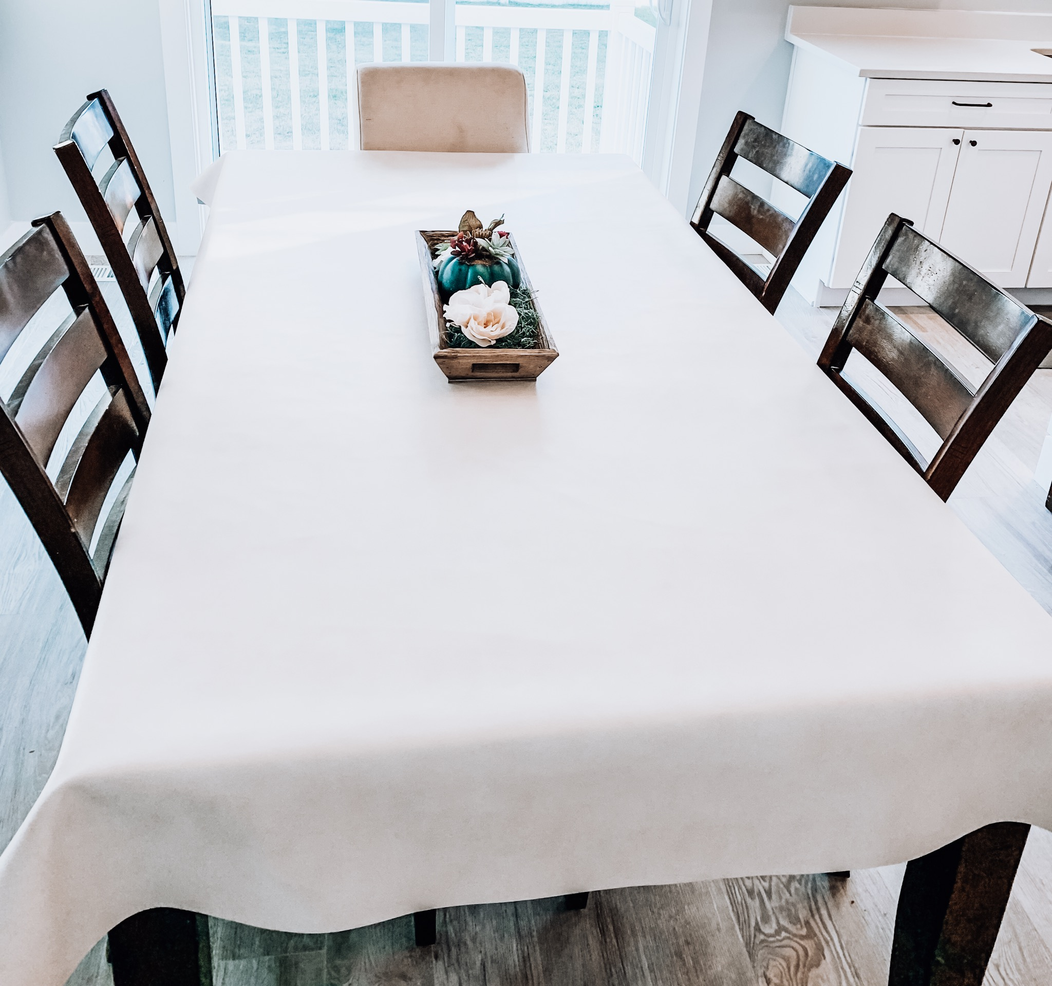 DIY Wipeable Tablecloth tutorial featured by top US sewing blogger, Kara Metta: Wipeable tablecloth in a dining room with 4 chairs and a centerpiece.