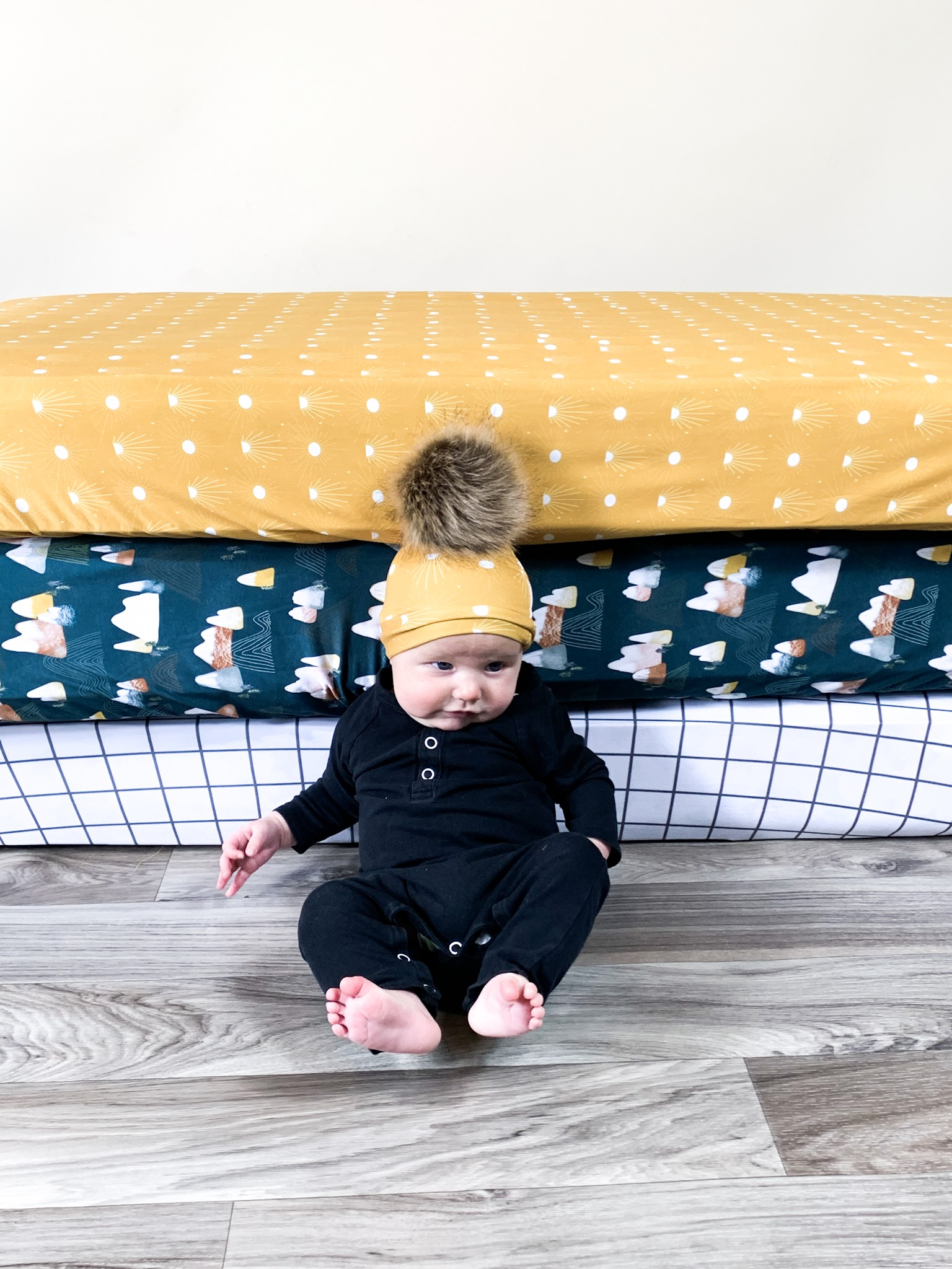 Three baby mattresses with fitted crib sheets behind a baby.