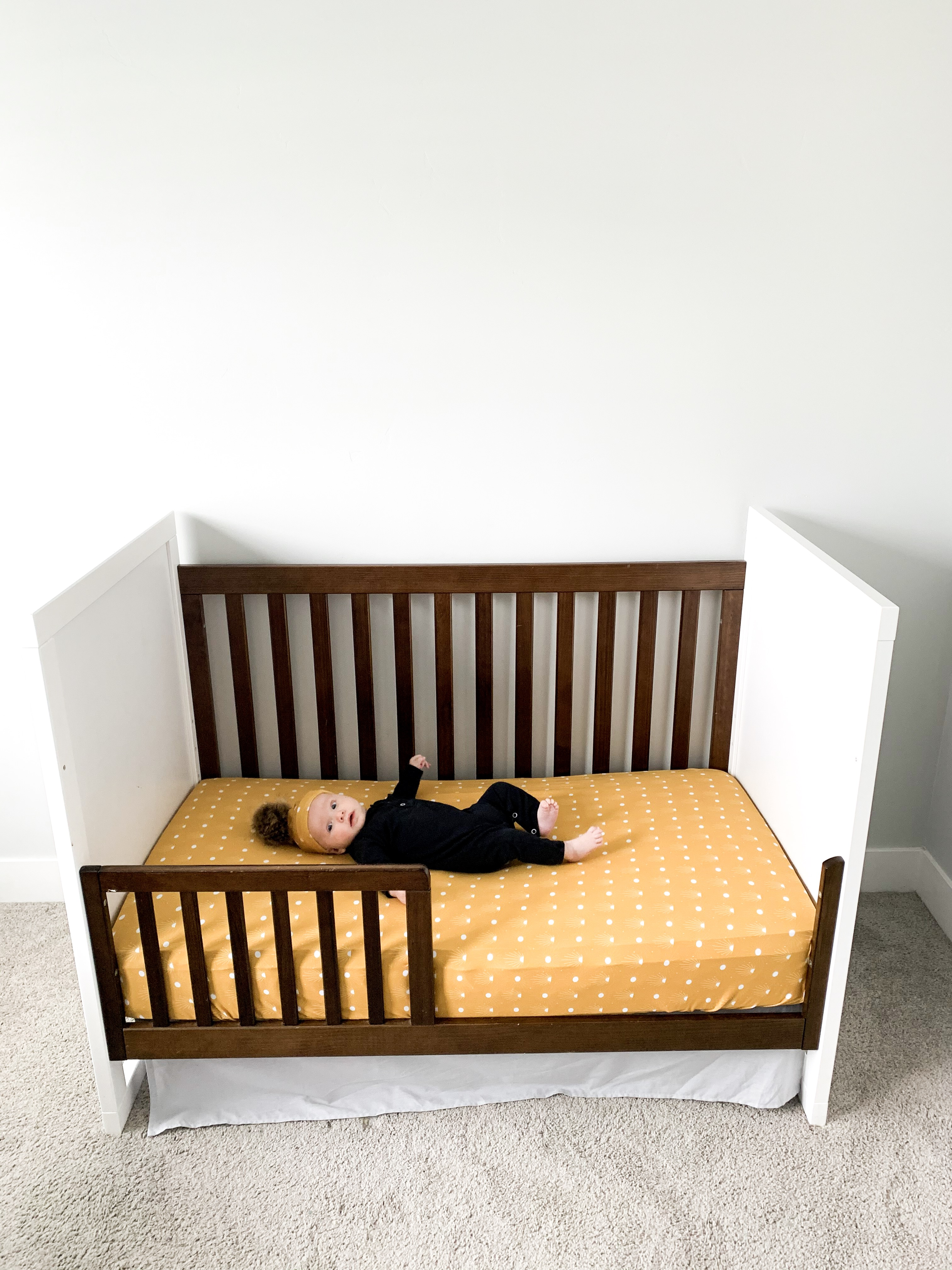 baby on a toddler bed with a yellow crib sheet.