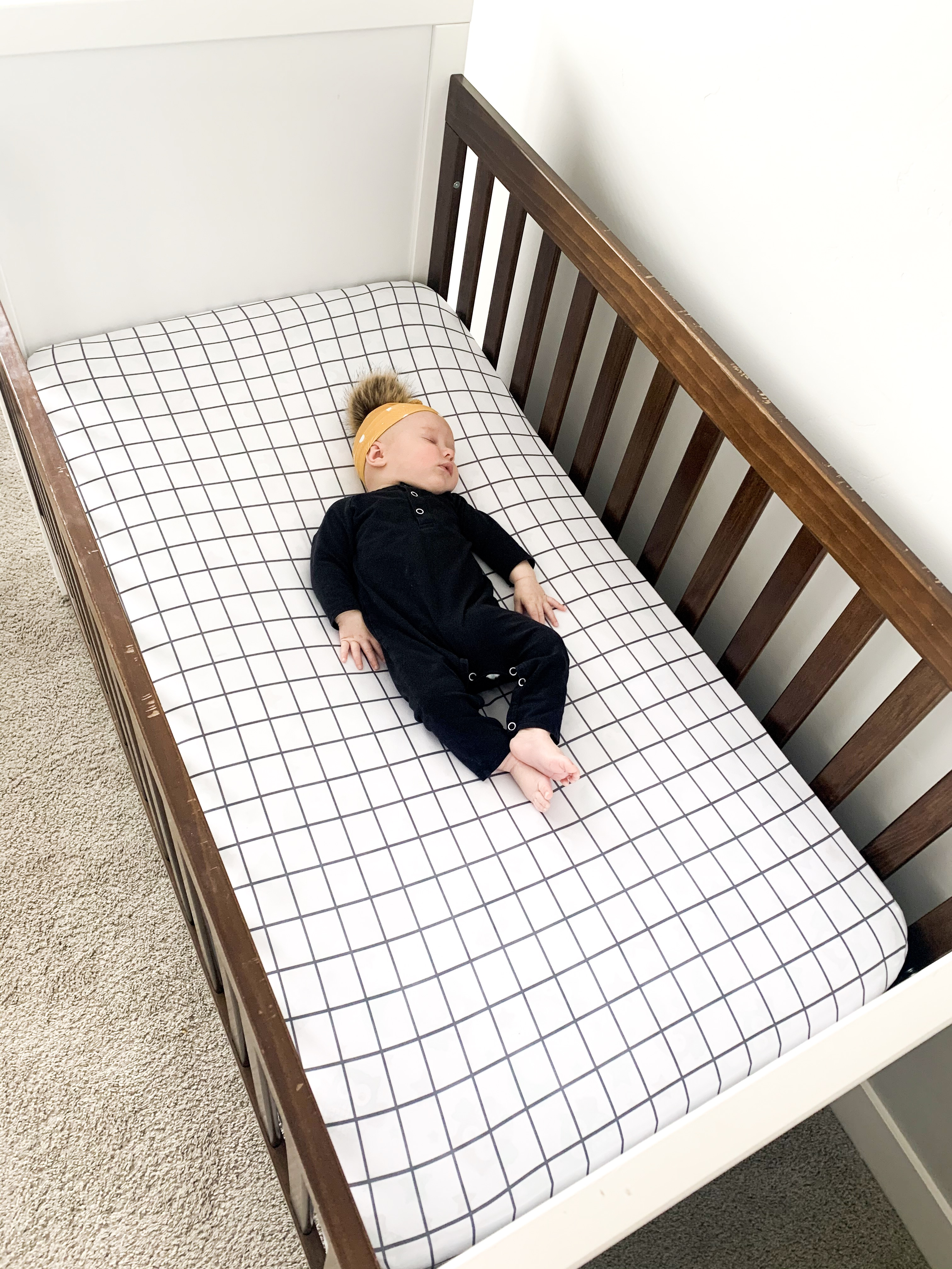 Baby sleeping on a fitted crib sheet.