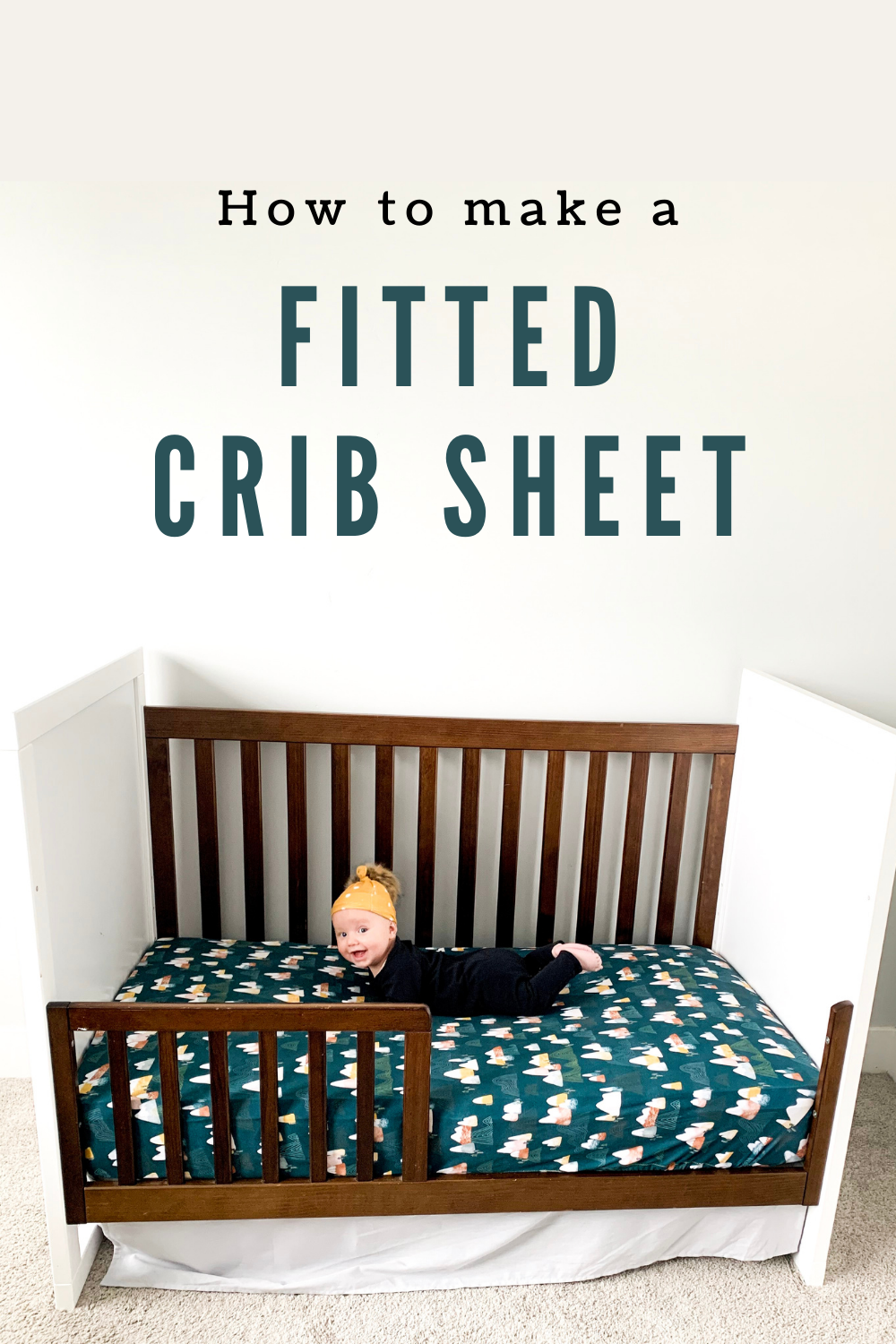 Baby on a modern crib with a green patterned fitted crib sheet.