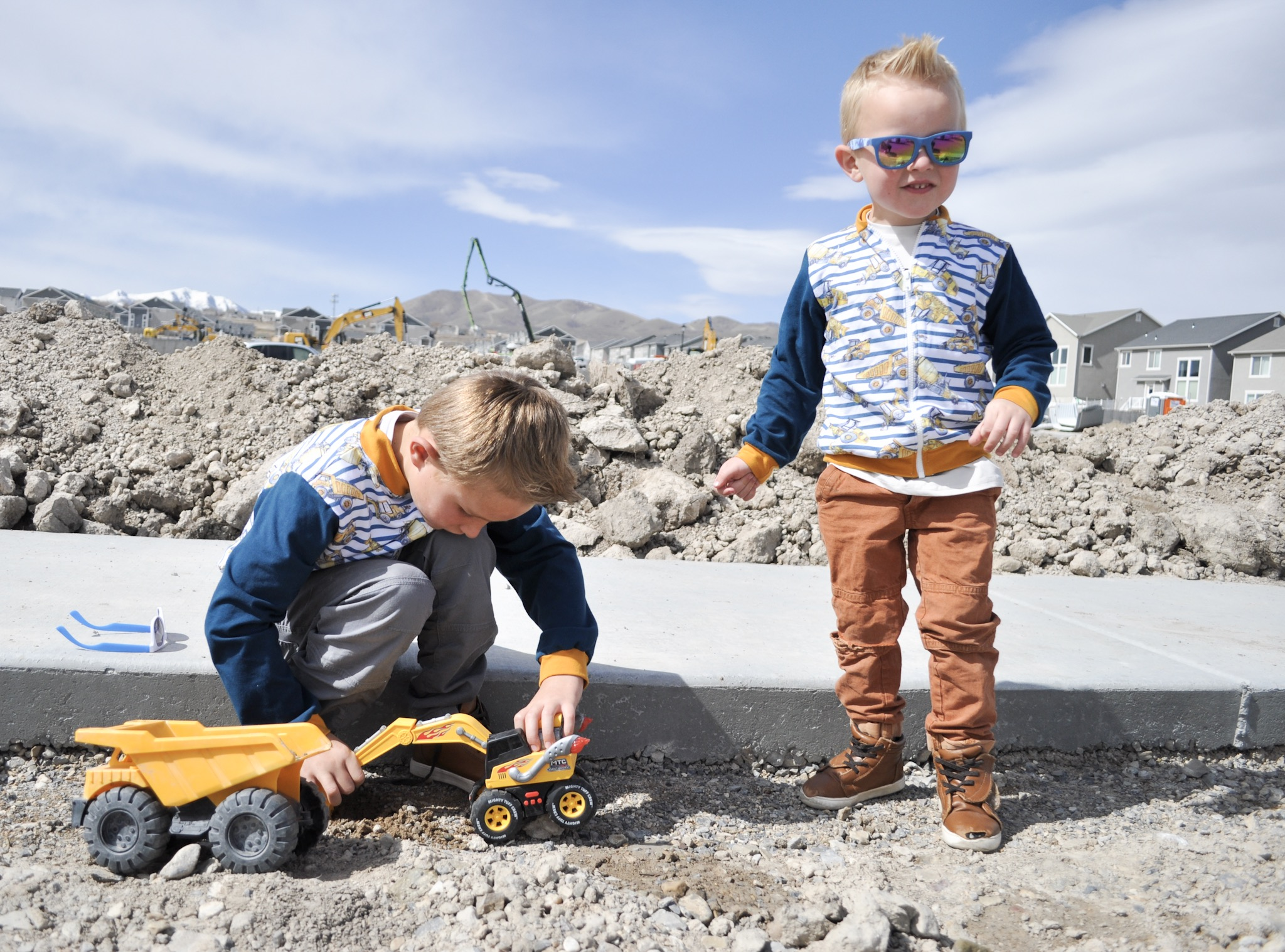 Two boys wearing matching jackets playing outside.