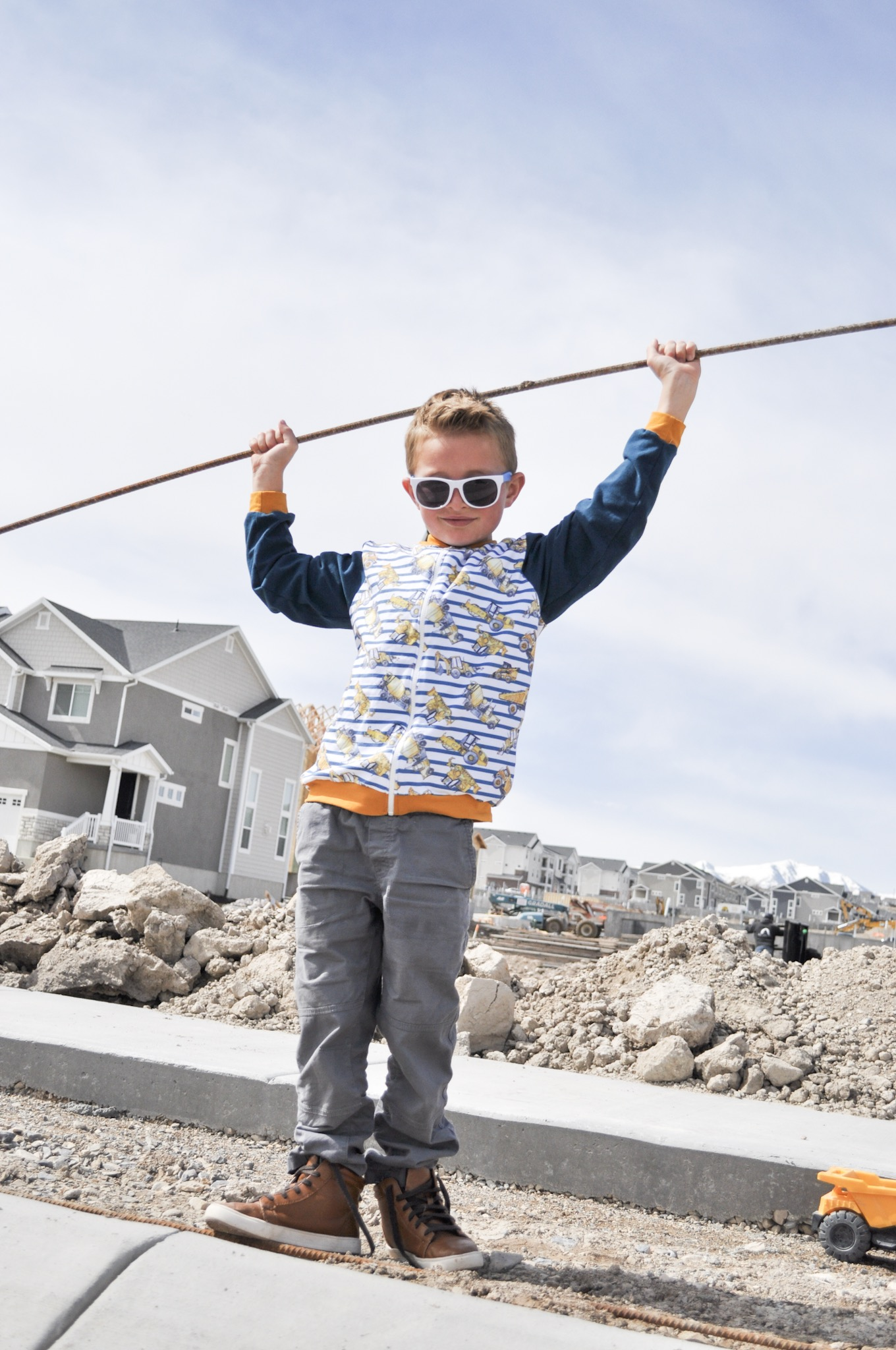 Boy wearing a bomber jacket is playing outside at a construction site.